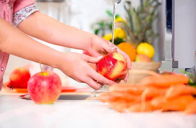 Девушка моет яблоко под водой